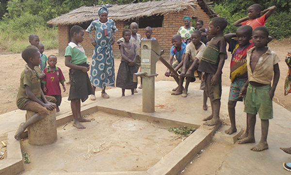 A group of children and 2 women standing and watching a boy use a well pump.