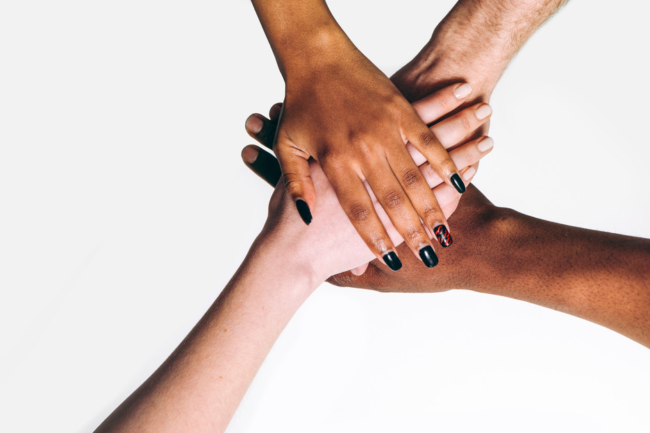 Photo of four hands stacked on top of each other, showing also their arms.  The hands are varied skintones, suggesting people of color and caucasian people.  Non-specific gender.  The top-most hand has fingernails painted black..