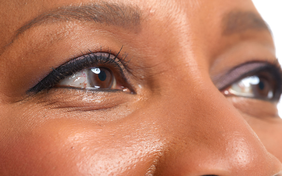 close-up photo of a brown-skinned woman, showing her eyes, eyebrows, top part of her nose, top part of her cheeks.  She has some makeup on her eyelids.