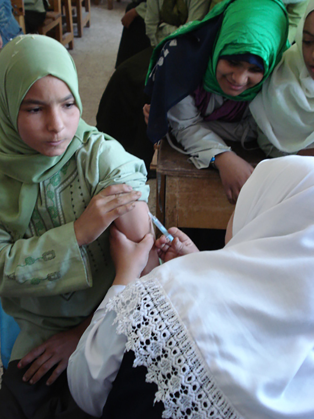 Photo of girl with light skin-tone and light green hijab receiving a shot via a hypodermic needle from a woman with light skin-tone and a white hijab.  Another girl wearing a dark green hijab is in a crowd of other children.