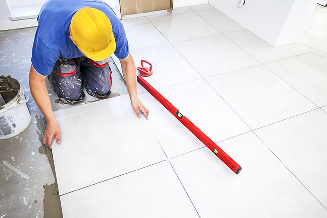 Laying tiles at home.jpg Construction worker laid floor tiles.jpg