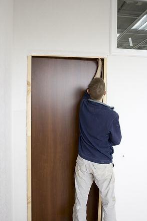 master installs door in office