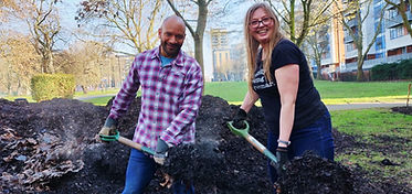 Shovelling mulch to nourish the flower beds
