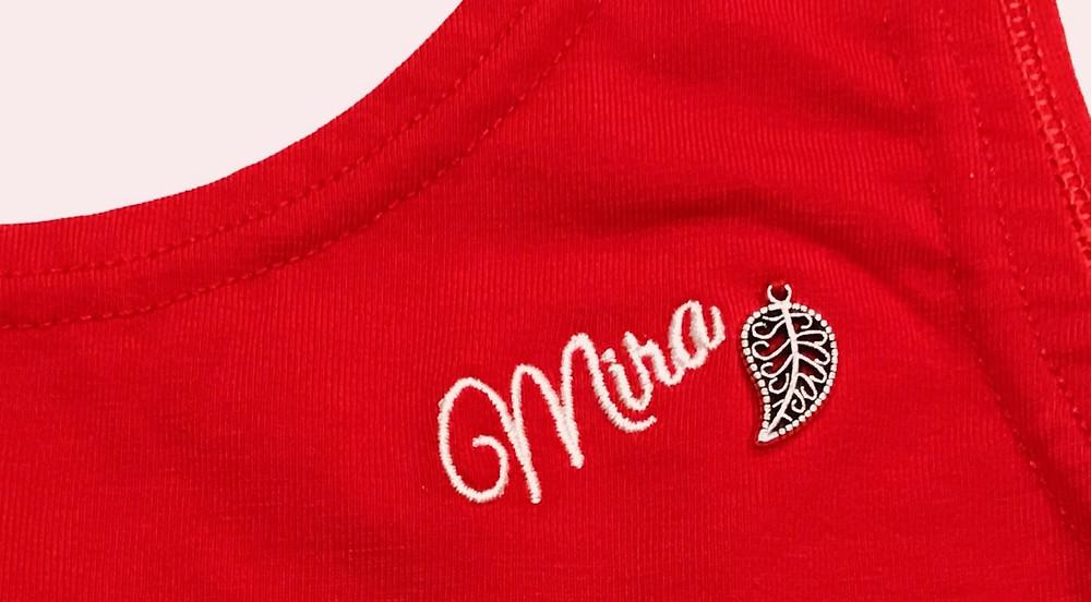 Бренд Mira на красном комбинезоне для йоги