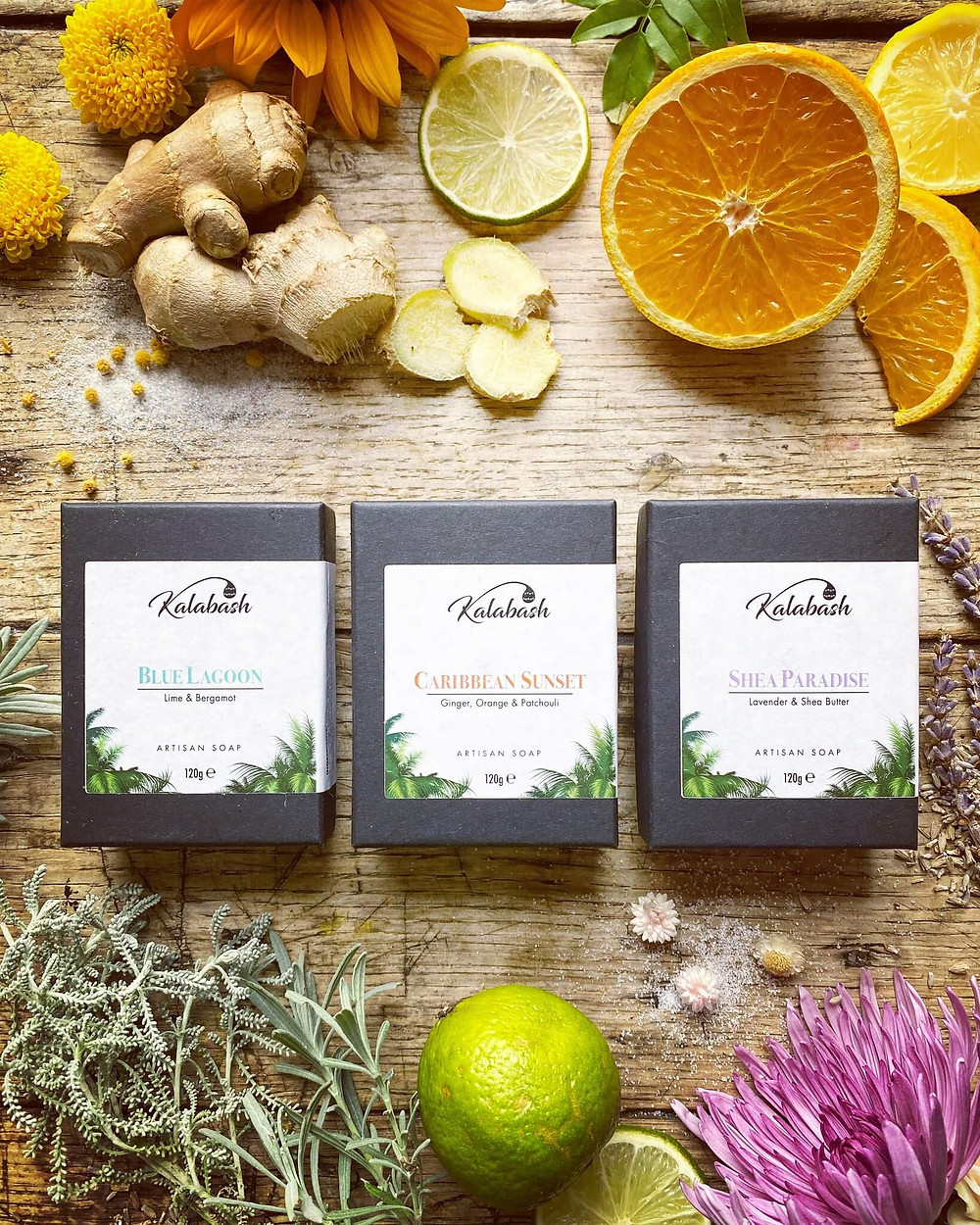 Boxed soap bars by Kalabash Bodycare flatly on wooden table with ginger, orange & lime slices, flowers and herbs including calendula and lavender