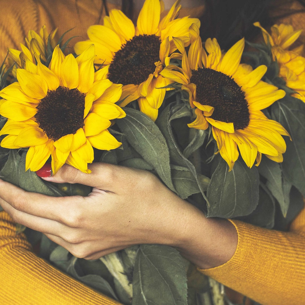 woman-in-gold-holding-big-yellow-sunflowers