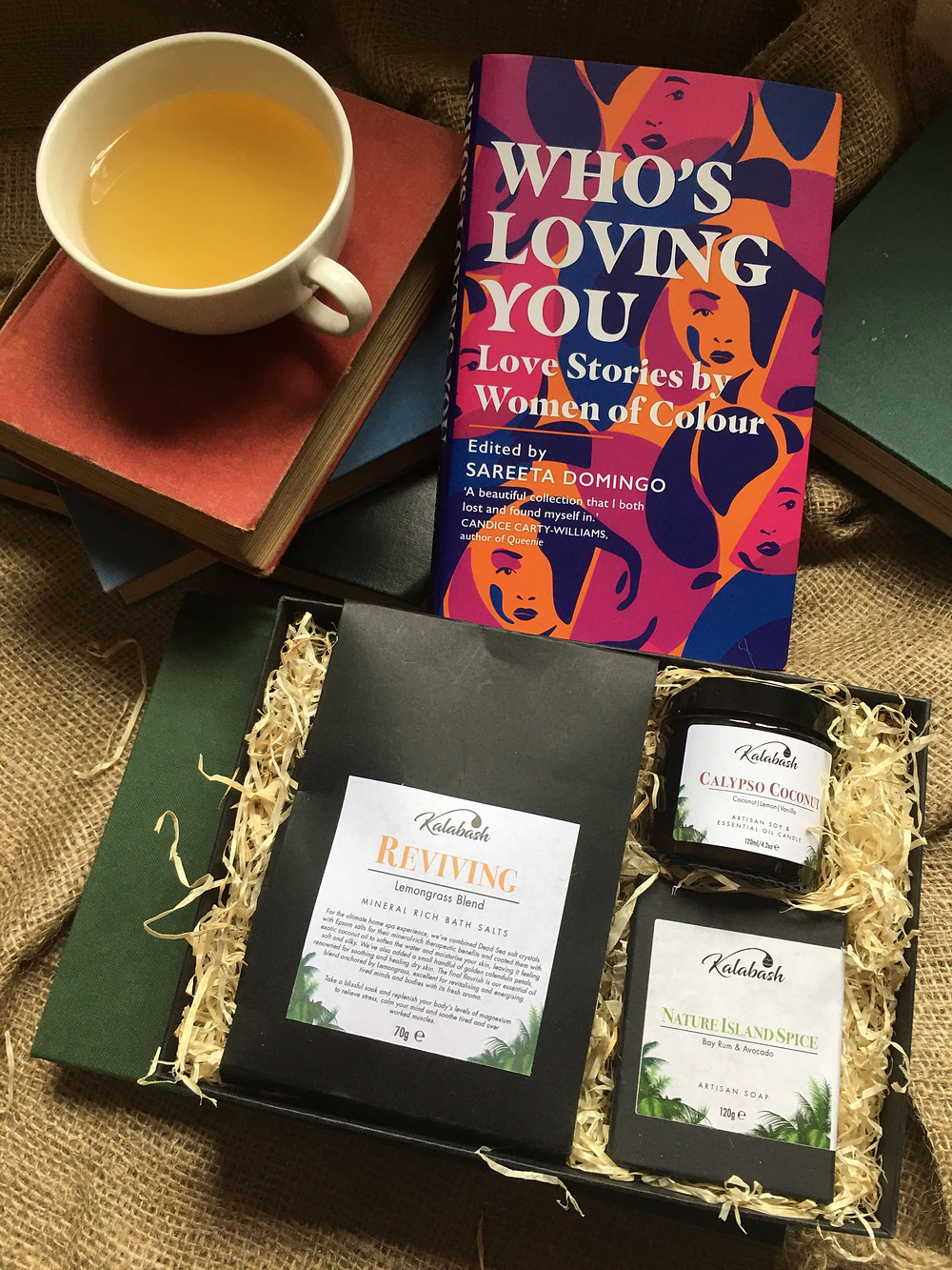 Kalabash Bodycare handmade soap gift set and Who's Loving You book, cup of tea and books on hessian background
