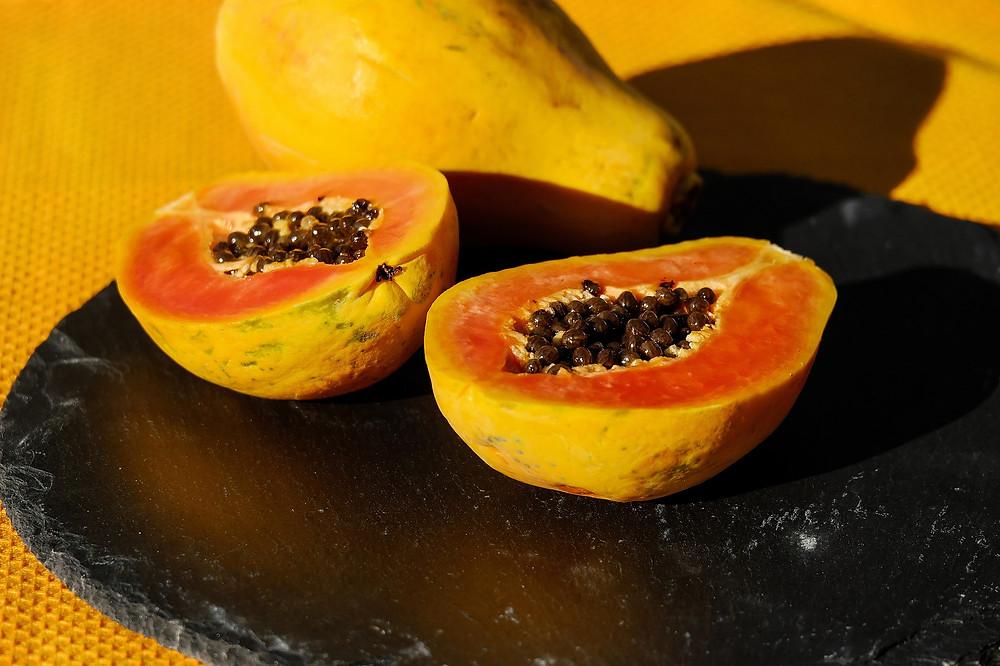 raw-papaya-on-black-plate-on-yellow-table-cloth