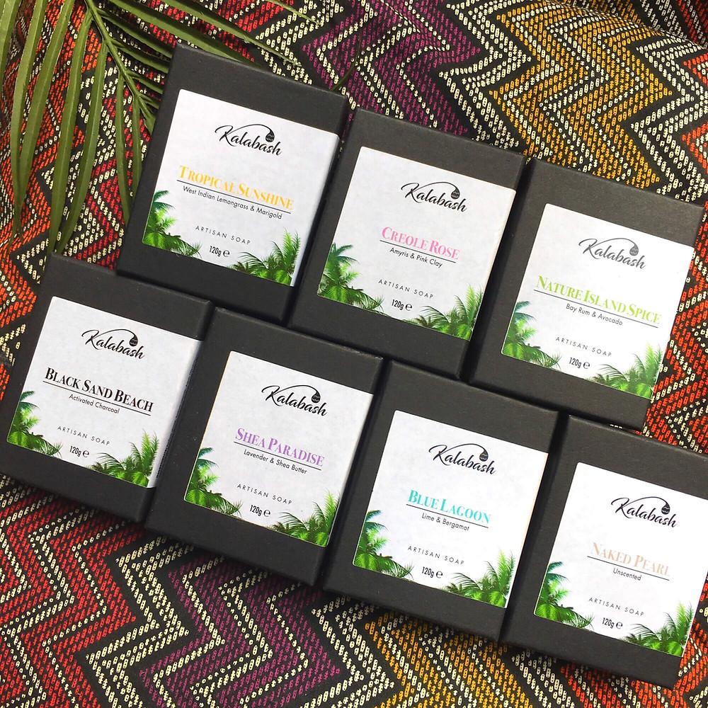 Kalabash soap range 7 bars of soaps in black boxes on ethnic fabric background.  Flatlay