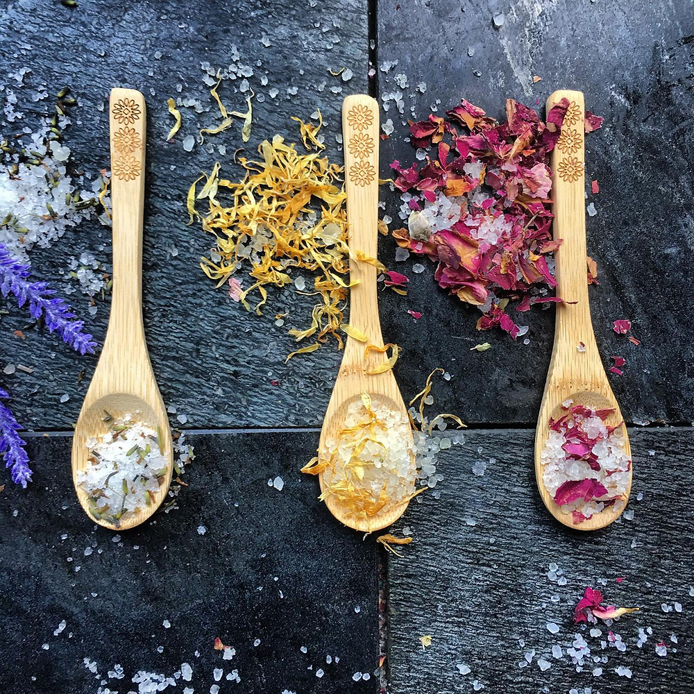 Three wooden spoons filled with Kalabash bath salts lavender calendula and rose petals on black slate background
