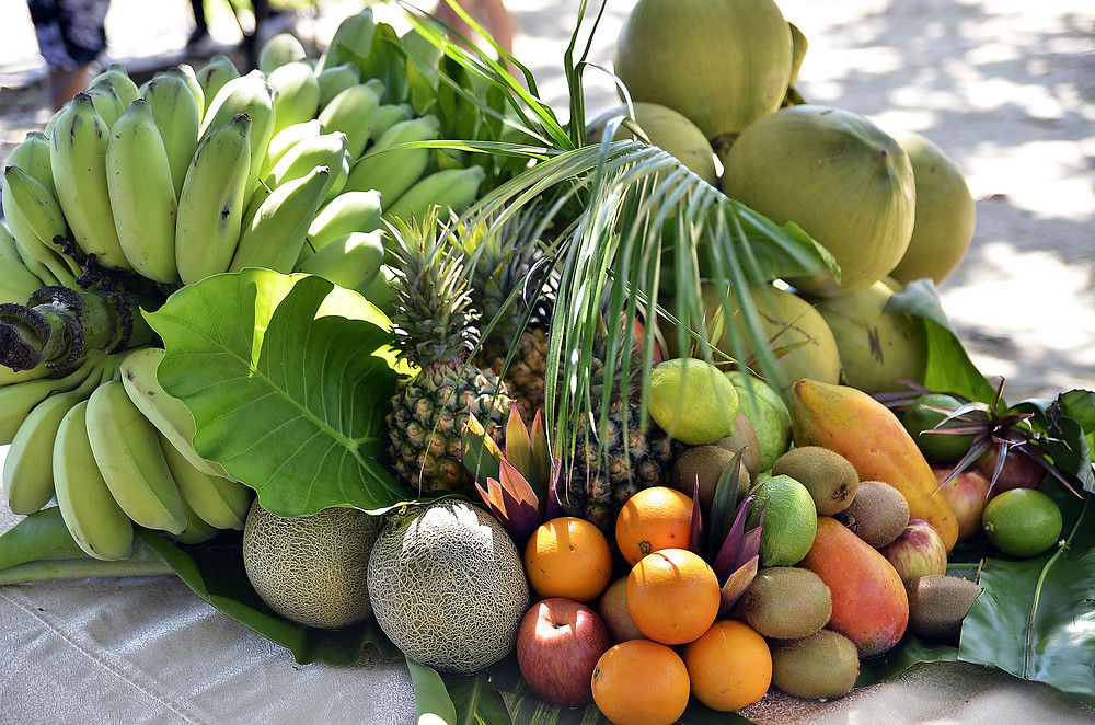 tropical-fruits-and-green-bananas-on-beach