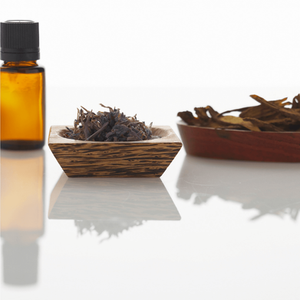 amber-bottle-of-essential-oils-and-dishes-of-herbs