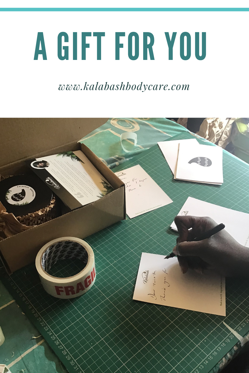 Dark skinned hand writing a thank you note with ink pen on cutting board with Kalabash Bodycare products and cards