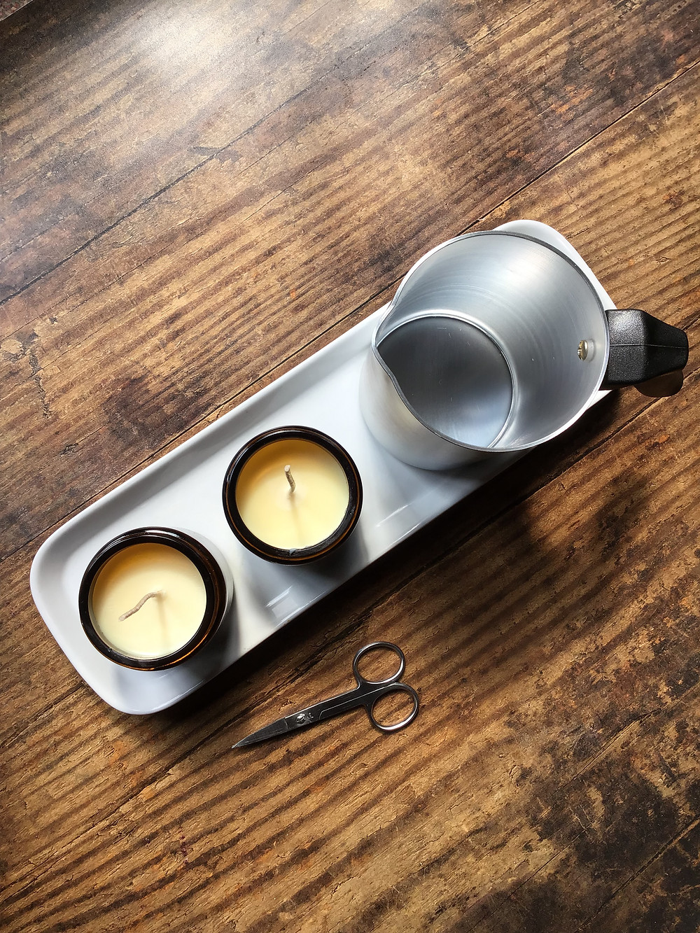 two soy candles in amber jars and candle jug on white tray on wooden surface with scissors