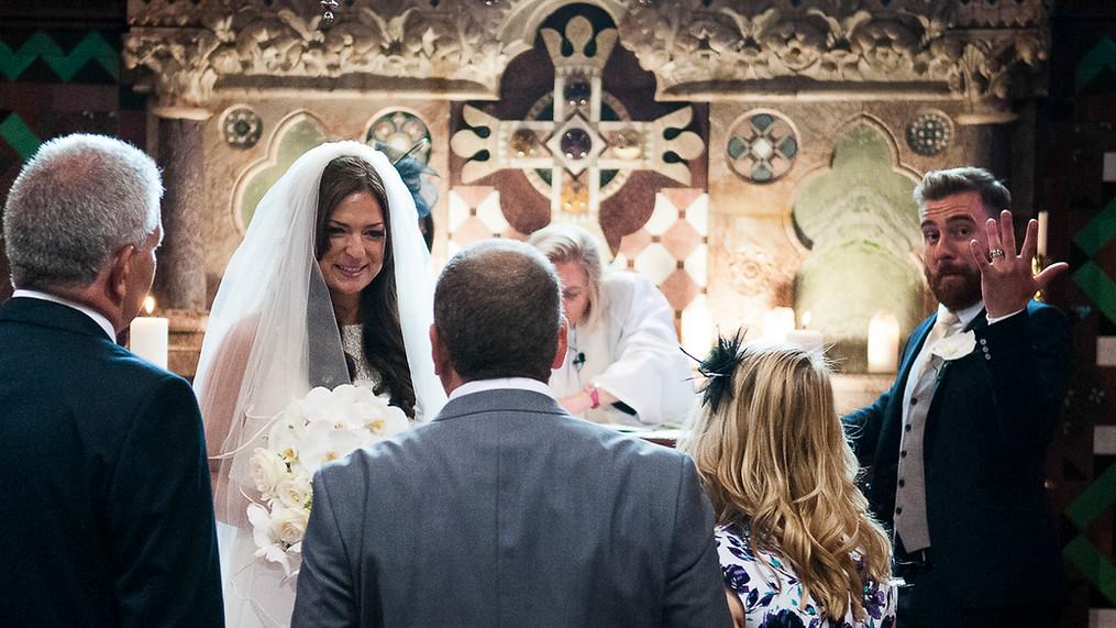 Portrait of newly wed male and female at the altar, man shows off his wedding ring.