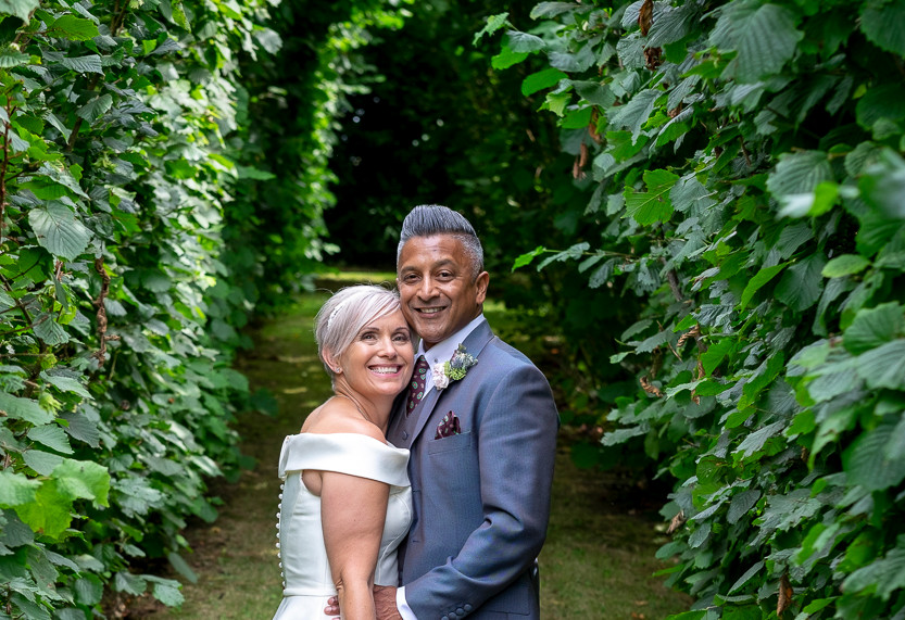 Portrait of newly wed male and female in a hedged avenue looking at the camera.
