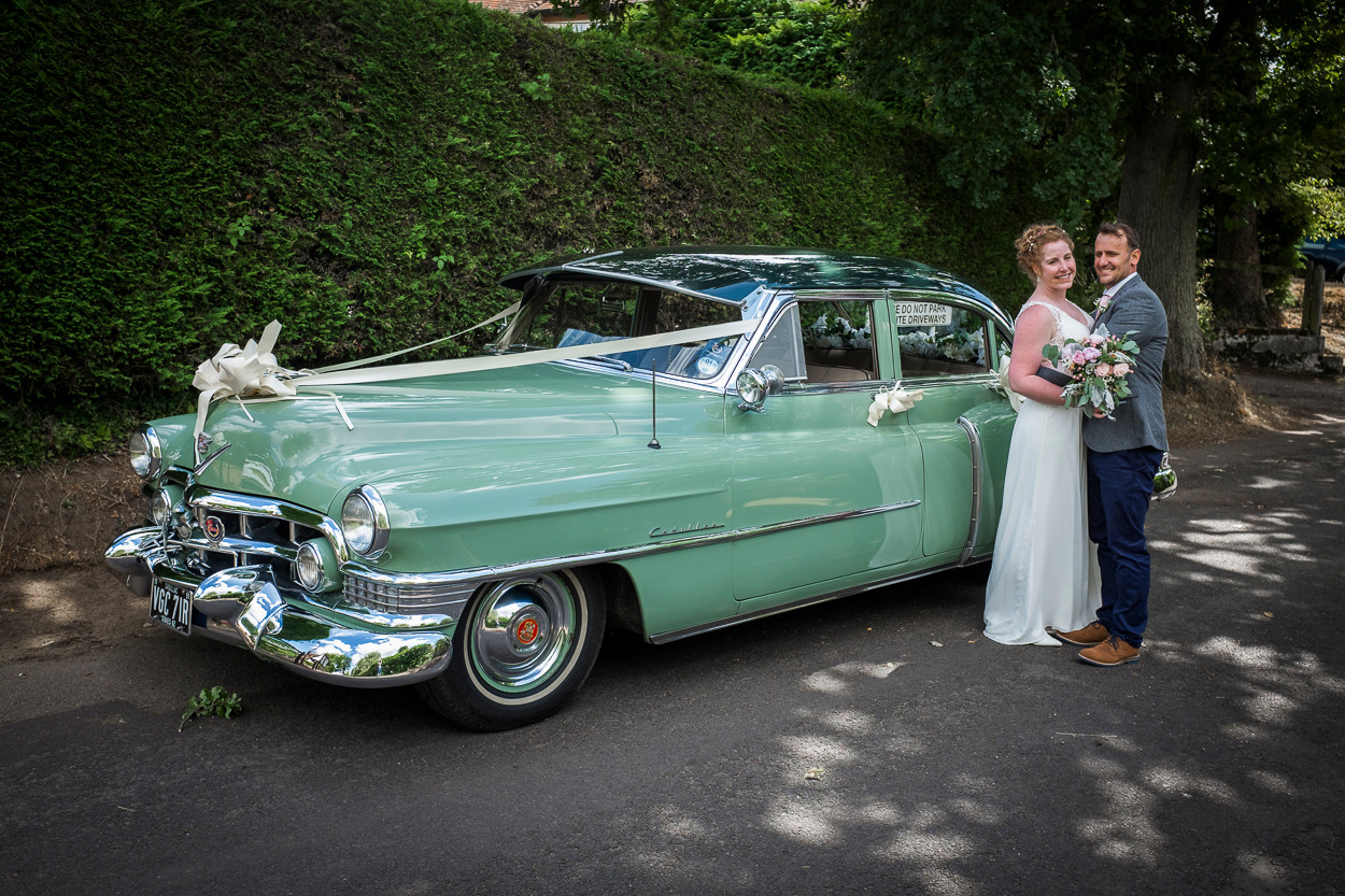 Portrait of newly wed male and female standing next to a 1950s car.