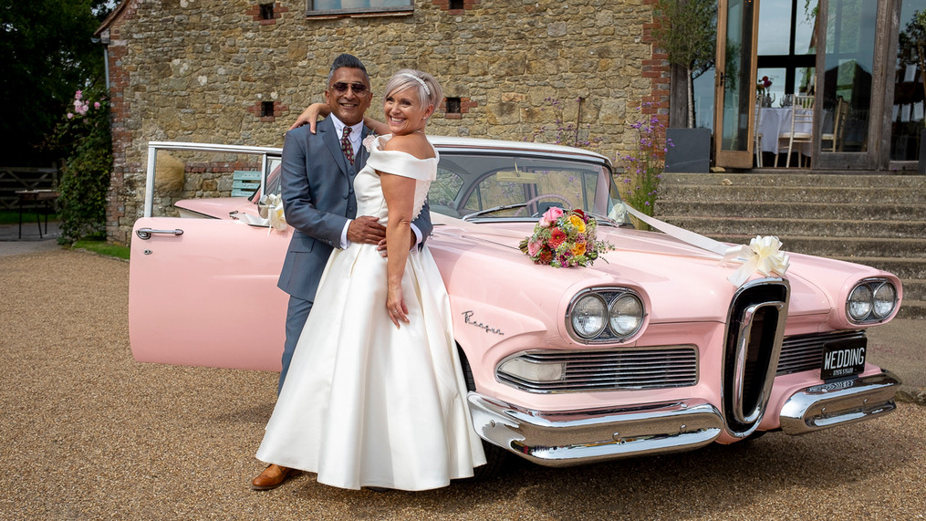 Portrait of newly wed male and female leaning on a 1950s Ford Edsel car, bouquet on bonnet.