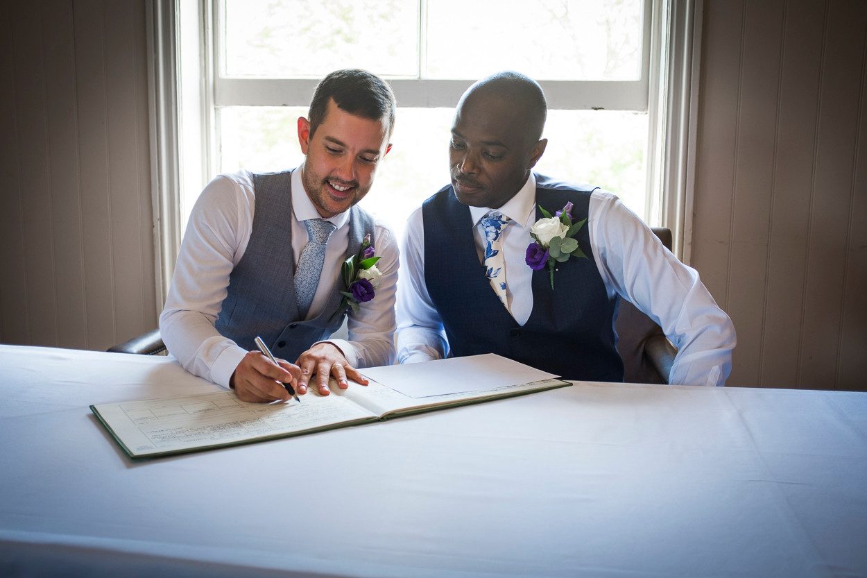 Portrait of two newly wed males signing their marriage certificate, the sun pours through window from behind.