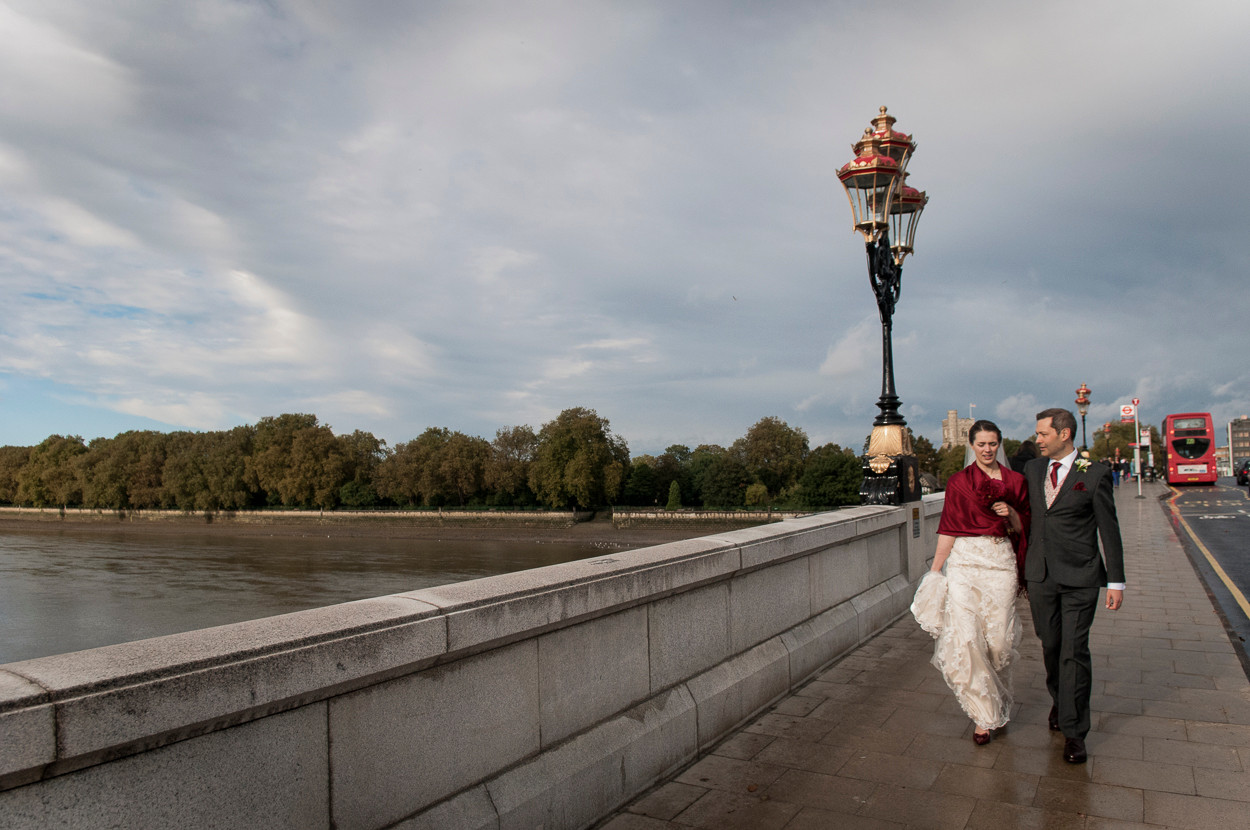 Portrait of newly wed male and female walk towards camera across Putney Bridge in London, England.