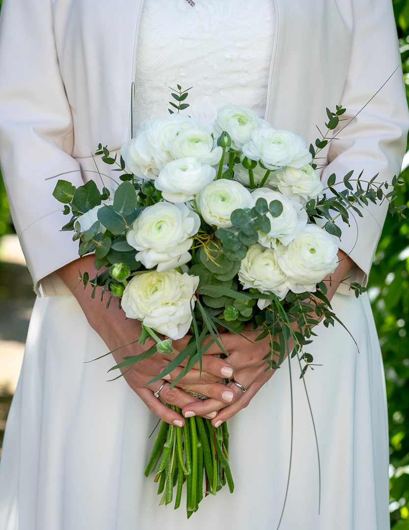 Close up of bride holing her bouquet at her waist.