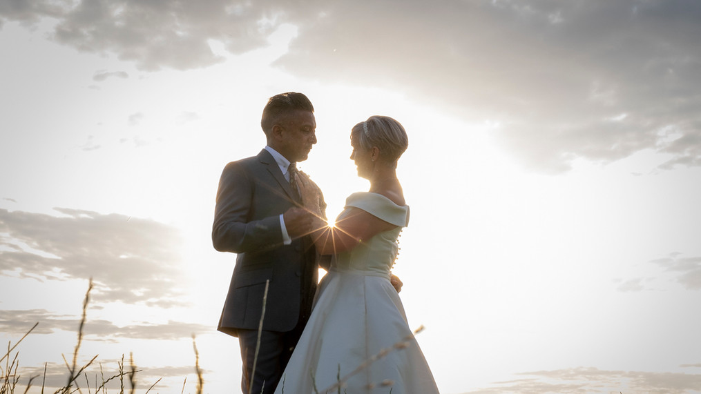 Portrait of newly wed male and female silhouetted against sunset.