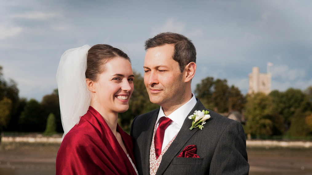 Portrait of newly wed male and female stand facing camera on Putney Bridge in London, England.