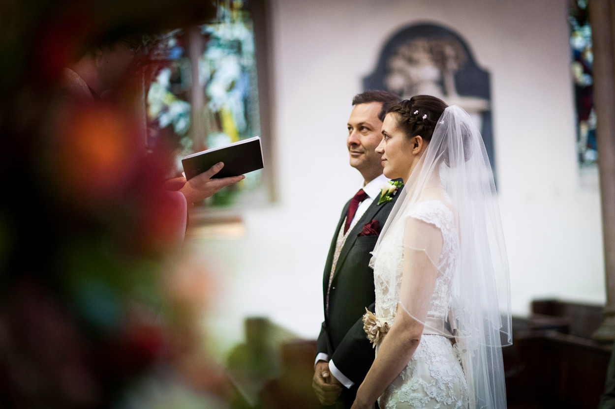 Portrait of newly wed male and female standing and listening to priest in a Catholic church.
