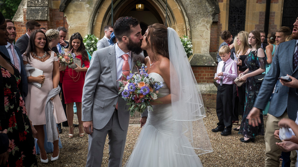 Portrait of newly wed male and female kissing outside the church.
