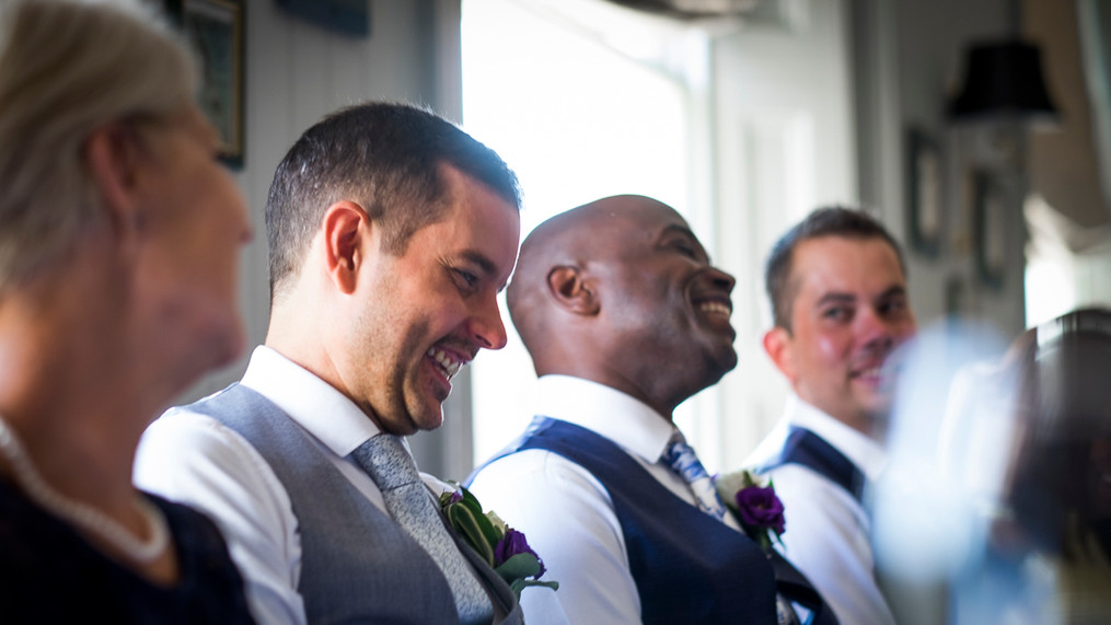 Portrait of two newly wed males laughing at speeches, the sun pours through window from behind.