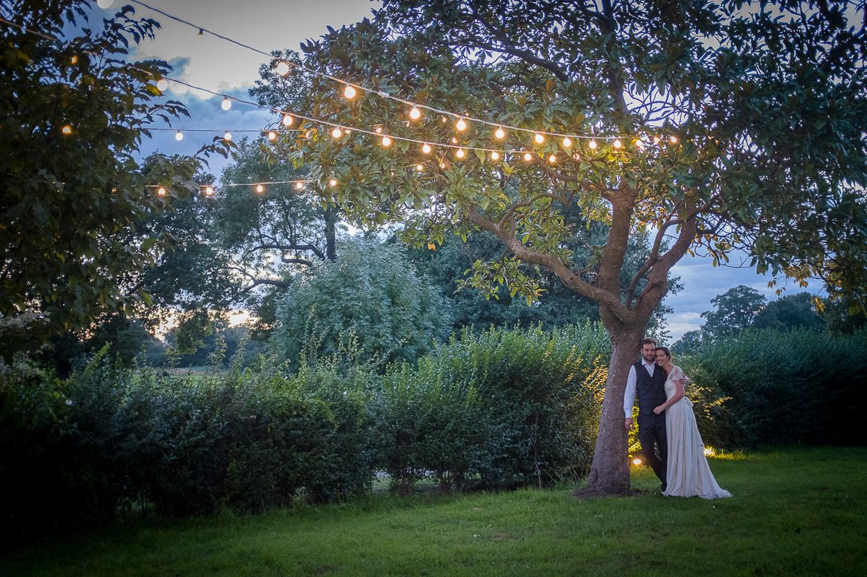 Portrait of newly wed male and female standing against a tree in the twilight, festoon lights the fill the trees.