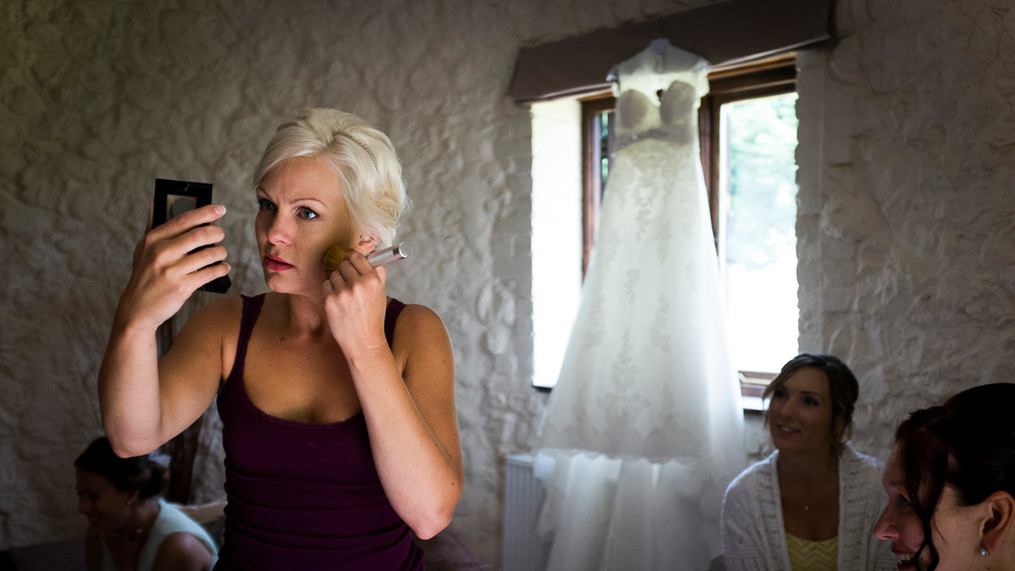 Bride applies make-up whilst holding a mirror, sun ours in from window behind.