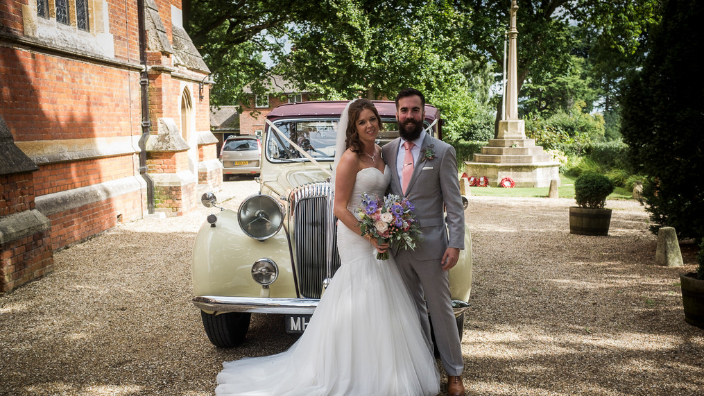 Portrait of newly wed male and female with vintage car outside the church.