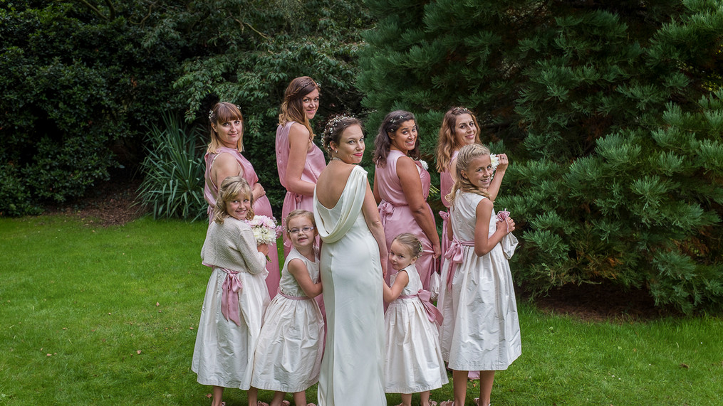 Bridal party stand facing away but are turning heads back towards the camera.