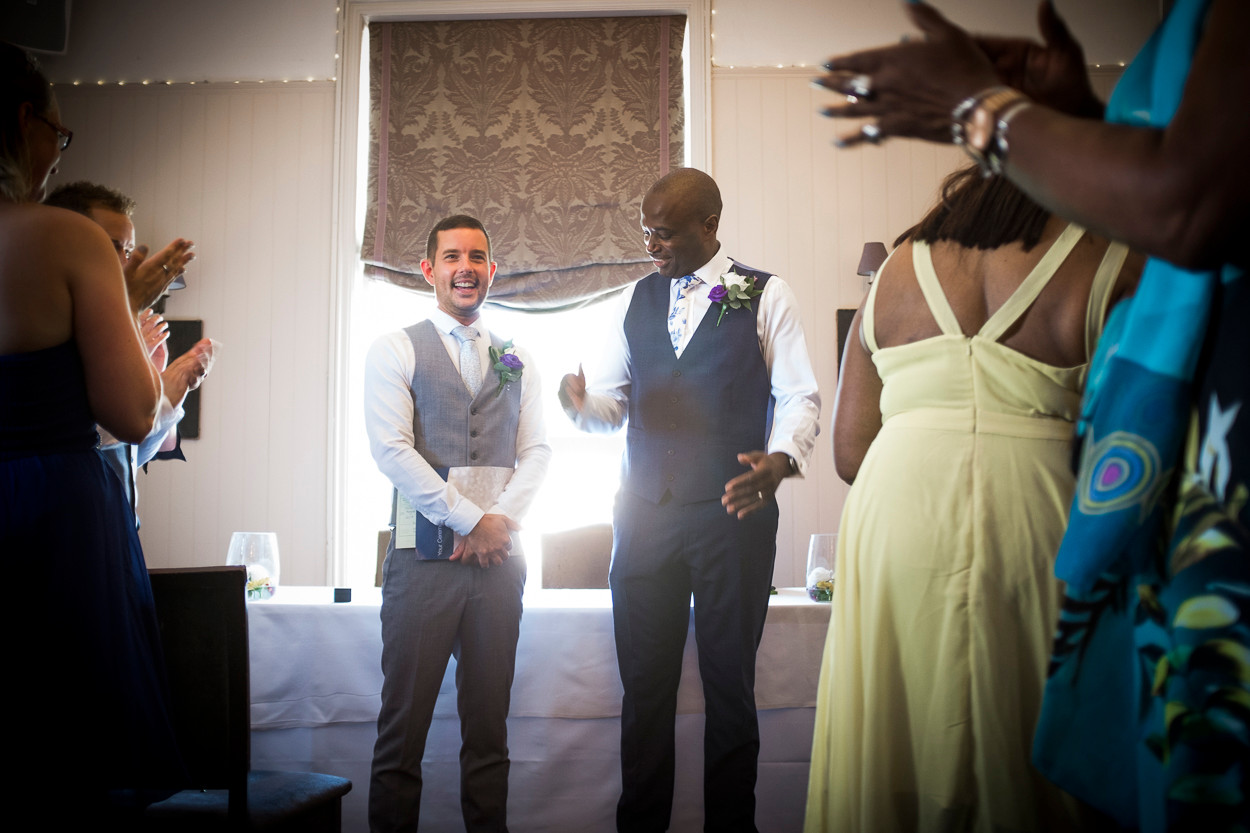 Portrait of two newly wed males, one punches the air with happiness whilst guests applaud and sun pours through window from behind.