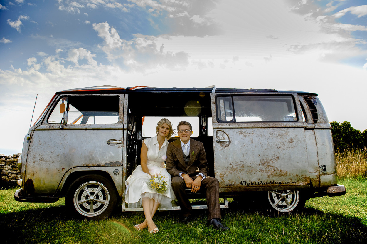 Portrait of newly wed male and female sit in side door of a paint less, metallic VW campervan.