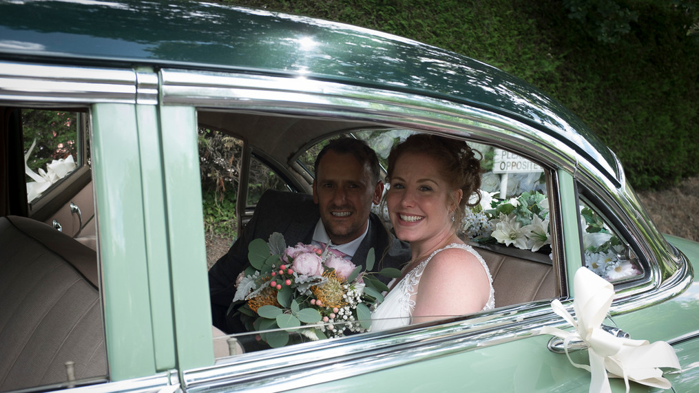 Portrait of newly wed male and female sitting inside a 1950s car.