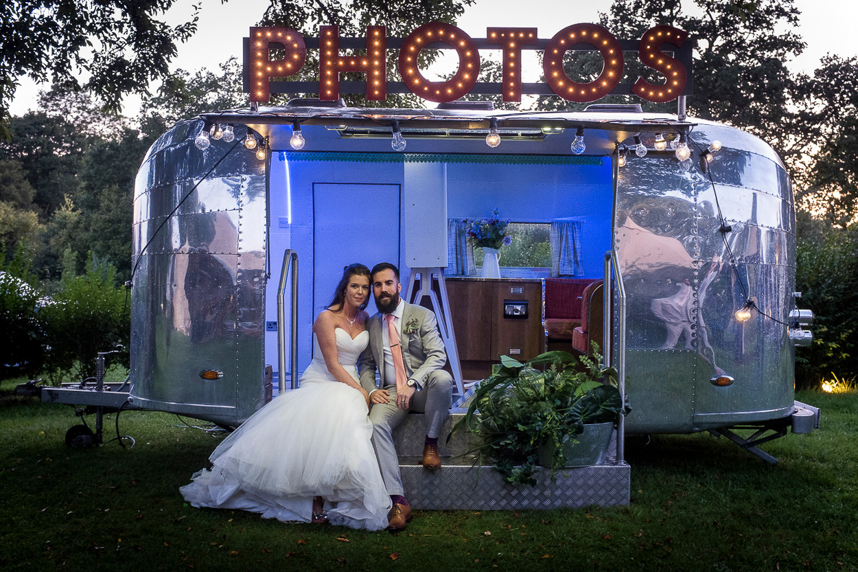 Portrait of newly wed male and female sitting on steps of Airstream photobooth caravan.