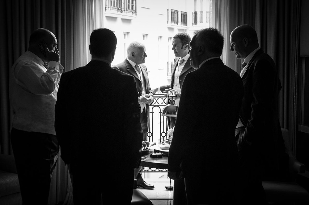 Groomsman gather and talk by an open window in a London hotel.