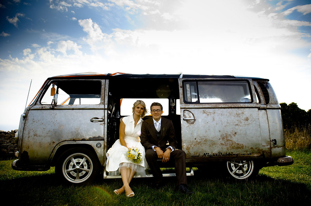 Bride and groom sit in a rust VW camper van.