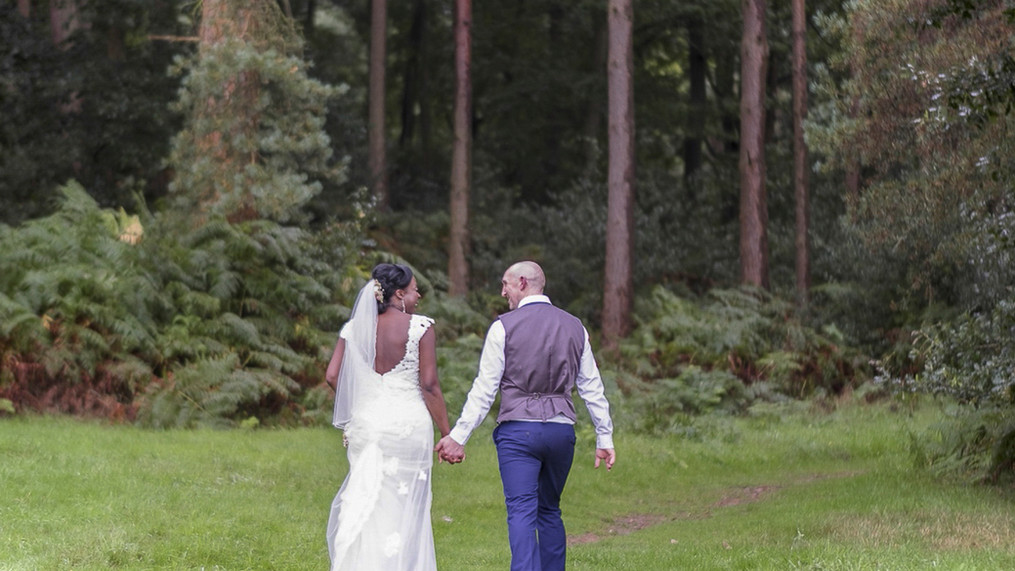 Portrait of newly wed male and female walking hand in hand towards a pine forest.