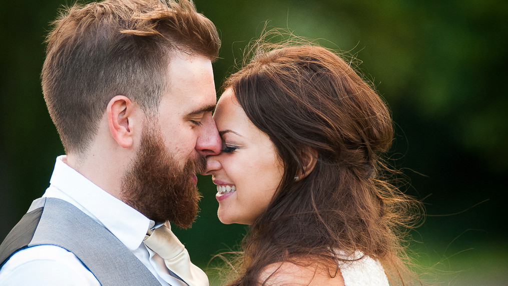 Portrait of newly wed male and female, heads together outside.