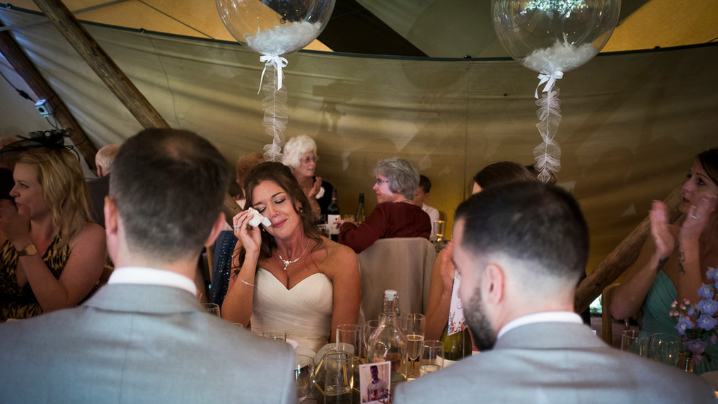 Bride at table surrounded by guests, sheds a tear at the speeches.