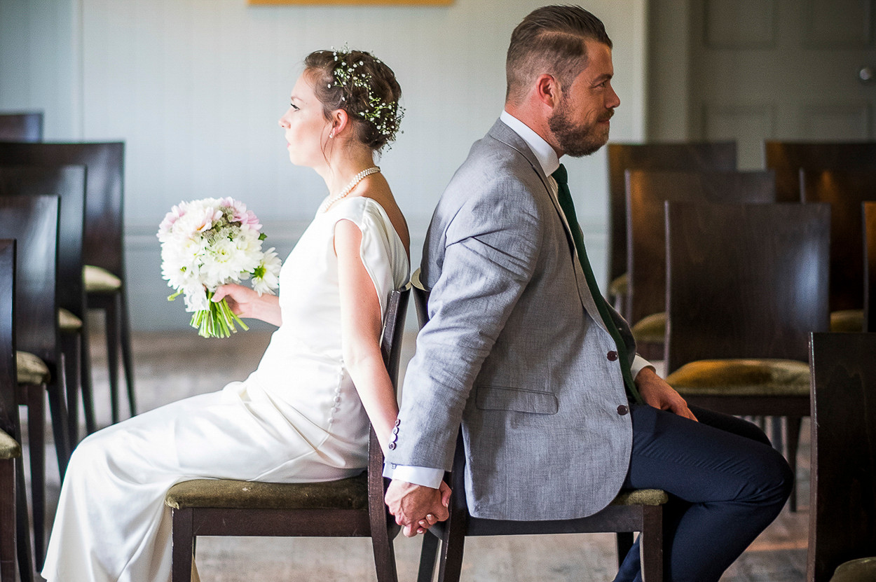 Portrait of newly wed male and female sitting back to back on a chair.