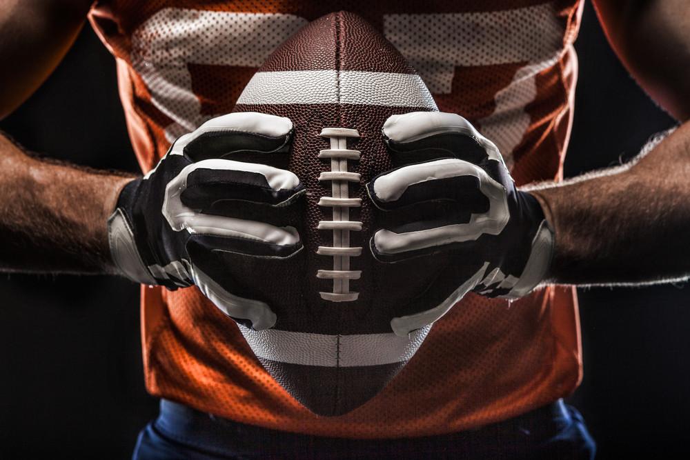 Grit football player gripping ball