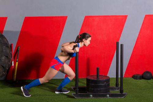 Girl pushing a weighted sled