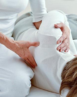 Shiatsu-Behandlung in Seitenlage, Daumendruck gezielt auf den Meridianpunkt Dünndarm 11.  © Ulrike Heinich