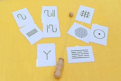 Praxisorientierte Neue Homöopathie, das Bild zeigt die Materialien, die bei der Praxisorientierten Neuen Homöopathie verwendet werden. Es ist eine Einhandrute, mit der energetische Ungleichgewichte (am Körper und bzgl. geistiger Einstellungen sowie Ängste) getestet werden oder die zum Testen von Lebensmittelunverträglichkeiten, etc. Verwendung findet. Und man sieht Kärtchen mit Zeichen/Symbolen. Diese Zeichen tragen eine bestimmte Schwingung in sich, durch die ein Ausgleich in der Imbalance erreicht werden kann. © Ulrike Heinich