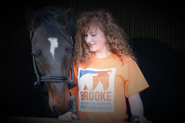Alanna Clarke Equestrian wearin a The Brooke T Shirt standing with her horse Katrina