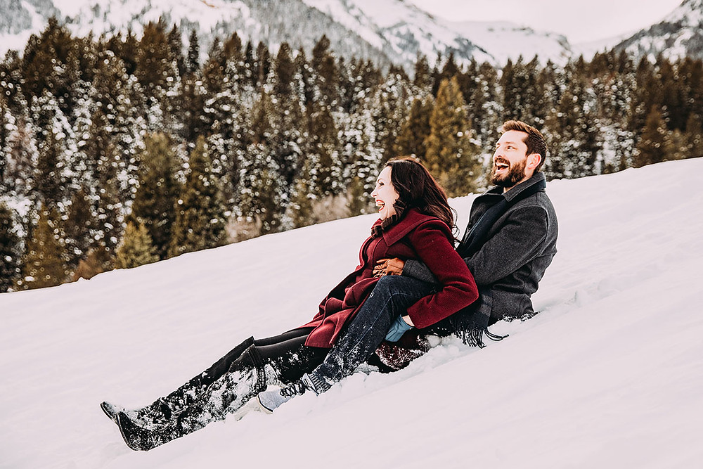 couple sliding down the snow covered mountian
